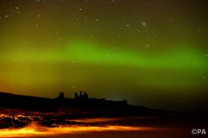 Aurora borealis lights up the sky over Dunstanburgh Castle in Northumberland, England
