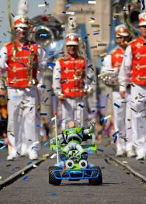 """The Buzz Lightyear toy that went into space took an Earthly spin through Disney's Magic Kingdom on the top of another """"Toy Story"""" character - RC. The ride down Disney's Main Street came complete with confetti and ribbons."""