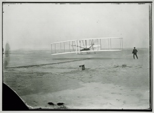 1903 Wright Flyer First Flight, Kitty Hawk, NC With Orville Wright at the controls and Wilbur Wright mid-stride, right, the 1903 Wright Flyer makes its first flight at Kitty Hawk, NC, 17 December, 1903